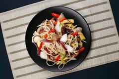 乌龙面铁锅面条用猪肉和胡椒,供食在黑色的盘子, f 库存图片