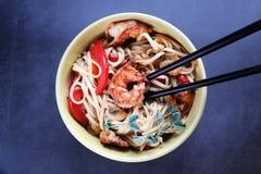 乌龙面面条用虾和菜在一个黄色碗在黑暗的背景 免版税库存图片