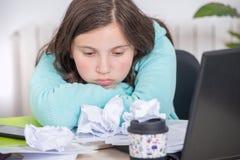 乏味十几岁的女孩做着她的家庭作业 免版税库存照片