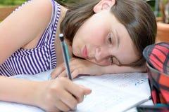 乏味十几岁的女孩做着她的家庭作业 库存照片