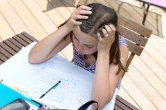 乏味十几岁的女孩做着她的家庭作业 免版税图库摄影
