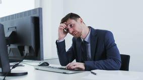 乏味和疲乏的商人看一台固定式计算机 股票录像