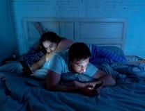 乏味夫妇在床上使上瘾对他们后忽略的巧妙的手机在晚上 免版税库存图片