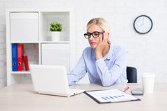乏味女商人与计算机一起使用在办公室 免版税图库摄影