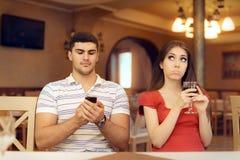 乏味女孩在与被他的智能手机占据心思的她的男朋友的一个日期 免版税图库摄影