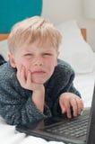 乏味孩子在联机他的卧室 免版税库存图片