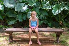 乏味小女孩坐一条长凳在天堂 库存图片