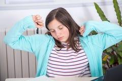 乏味少年女孩做着她的家庭作业 库存照片