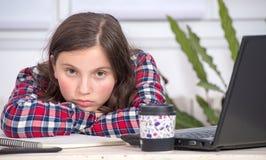 乏味少年女孩做着她的家庭作业 免版税库存照片