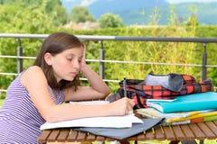 乏味少年做着她的家庭作业 免版税库存照片