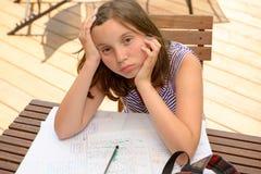 乏味少年做着她的家庭作业 免版税库存图片
