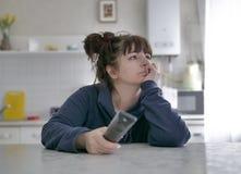 乏味年轻女人与遥控坐厨房的被弄脏的背景 库存照片