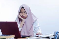 乏味年轻女人在办公室与膝上型计算机一起使用 图库摄影