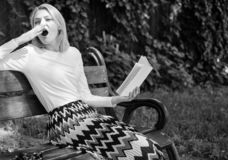 乏味文学 放松在庭院阅读书的妇女打呵欠的白肤金发的作为断裂 女孩坐放松与书的长凳 免版税库存图片