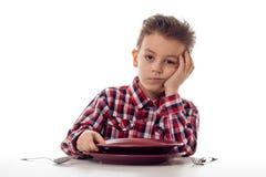 乏味男孩在桌上 免版税图库摄影