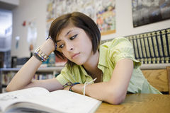 乏味高中学生在图书馆里 图库摄影