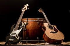 乐器、大鼓桶声学吉他和低音吉他在黑背景 库存图片