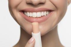 乐观女孩应用低变应原的唇膏 免版税库存照片