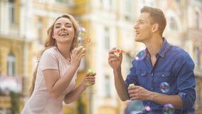 乐观年轻夫妇吹的泡影和一起笑,浪漫日期 免版税库存图片