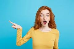 乐趣和人概念-愉快的有指向手指和冲击的姜红色头发女孩特写画象  库存照片