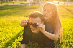 乐趣和爱概念与躺下在草和微笑的一对年轻夫妇 库存照片