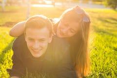 乐趣和爱概念与躺下在草和微笑的一对年轻夫妇 免版税图库摄影