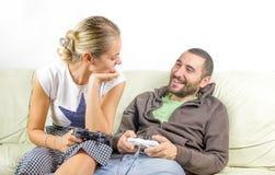 乐趣夫妇看彼此-打电子游戏 免版税图库摄影
