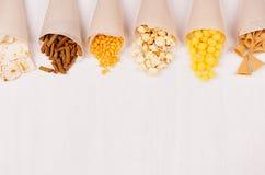 乐趣新夏天快餐背景-快餐烤干酪辣味玉米片,油煎方型小面包片,芯片,玉米粉薄烙饼,在工艺纸锥体的玉米花在白木委员会 免版税库存照片