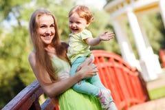 乐趣母亲和女儿在桥梁的公园 库存照片