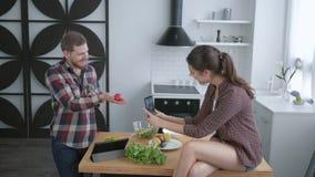 乐趣烹调,拍在手机和鬼脸的疯狂的年轻夫妇selfie照片,当烹调健康菜沙拉为时 影视素材