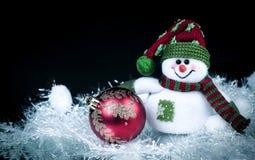 乐趣玩具雪人和圣诞节球在黑背景 免版税图库摄影