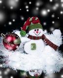 乐趣玩具雪人和圣诞节球在黑背景 免版税库存照片