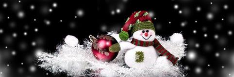 乐趣玩具雪人和圣诞节球在黑背景 免版税库存图片