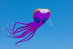 乐趣,巨型紫色章鱼风筝, 100英尺长,飞行在蓝天下 免版税库存图片