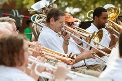 乐队成员戏剧伸缩喇叭和喇叭在小镇游行 库存照片