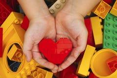 乐高红色心脏在儿童手上 免版税库存图片
