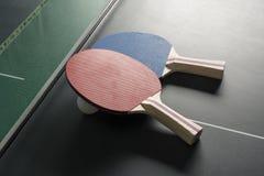 乒乓球在表,两个上用浆划在同样旁边,苛刻的照明设备 免版税库存图片
