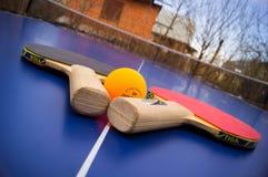 乒乓球球拍和一个球在桌上 免版税图库摄影