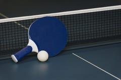 乒乓球球拍和球和网在一个蓝色球台上 库存照片