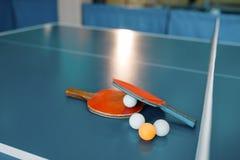 乒乓球球拍和球在比赛表上与网 免版税库存照片