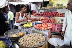 乔德普尔城,印度, 2010年9月10日:卖蔬菜和水果在一个localstreet市场上的年轻人在乌代浦 免版税图库摄影