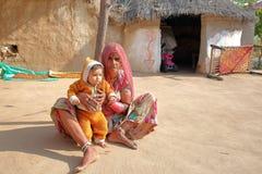 乔德普尔城,拉贾斯坦,印度- 2017年12月16日:一个老妇人的画象有一个婴孩的在乔德普尔城附近的一个Bishnoi村庄 免版税库存照片