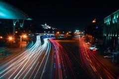 乔治亚,第比利斯- 05 02 2019年 - 汽车加速在公益霍尔旁边的高速公路的光踪影 的总统府 库存照片