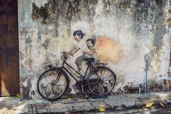 乔治城,槟榔岛,马来西亚- 2018年4月20日:自行车的公开街道艺术命名的孩子绘了在` s两点燃的墙壁上的3D 库存图片