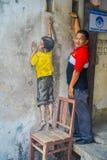 乔治市,马来西亚- 2017年3月10日:摆在与街道男孩艺术街道画的未知的人一把椅子的在乔治市 免版税库存照片