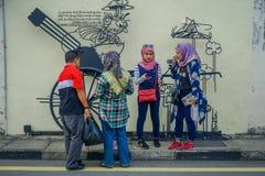 乔治市,马来西亚- 2017年3月10日:支持大炮街道画、街道艺术和铁的未知的回教游人 库存照片