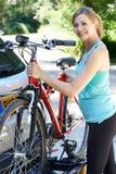 乘从机架的成熟女性骑自行车者登山车在汽车 图库摄影