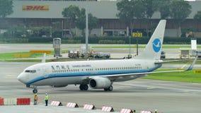 乘出租车在樟宜机场的厦航波音737-800地方喷气机 免版税库存照片