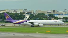 乘出租车在樟宜机场的泰航空中客车A340-600方形字体喷气机 免版税库存照片