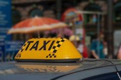 乘出租车在汽车屋顶的盖帽反对城市 库存图片